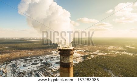 Heat electric station in winter. Aerial view. From above. Power station in a forest in sunny weather. Pipe with smoke close up