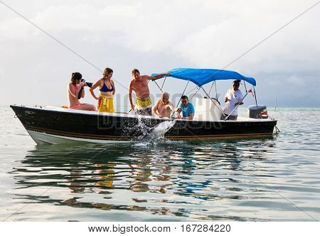 CAYE CAULKER, BELIZE- DEC 19, 2015: Tourists feeds fish from boat on Dec 19, 2015 in Caye Caulker island, Belize.