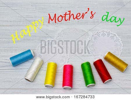Bobbins with colorful threads on old wooden table background. Happy mother's day concept
