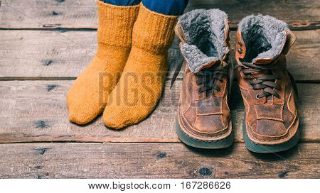 Feet wearing wool socks next to winter fur boots on the wooden floor. Color toning