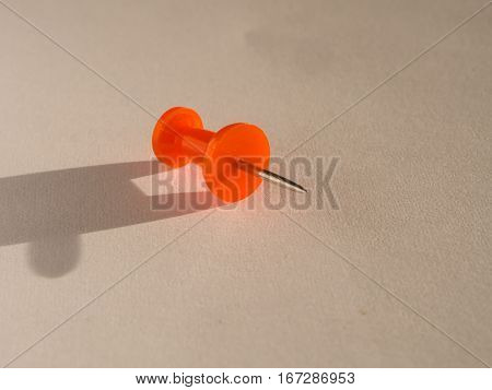 placeholder colored pin stuck on a white sheet of paper