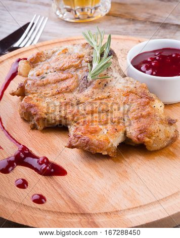 Fried pork steak served on wooden board with cranberry sauce