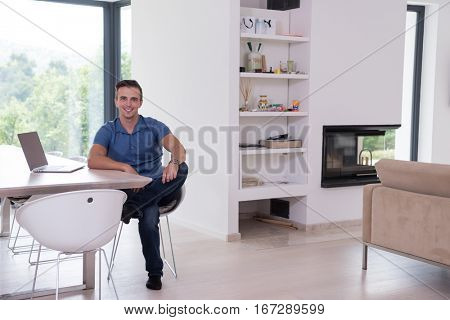 Young man with his laptop computer at his luxury modern home, smiling