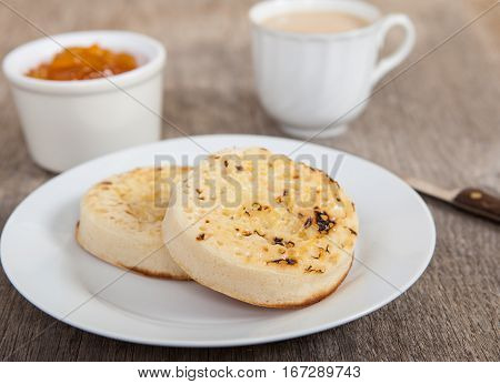 Hot toasted crumpets on the wooden table with blueberries and jam on the back
