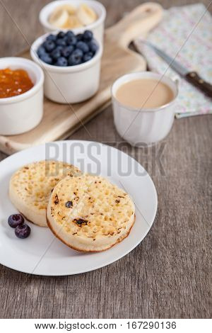 Hot toasted crumpets on the wooden table with blueberries and jam on the back selective focus