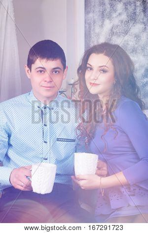 beautiful couple in love in blue with cups in hands on a background of a winter window