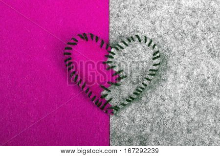 stitched broken felt heart on a on a two-color background