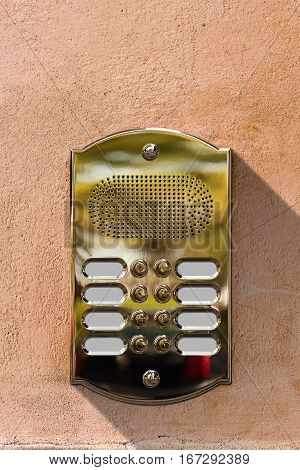 Detail of a golden intercom with eight doorbell buttons with empty copy space on a wall. Italy