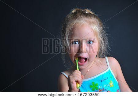 little girl brushing her teeth, girl brushing her teeth, funny little girl brushing her teeth, dark background