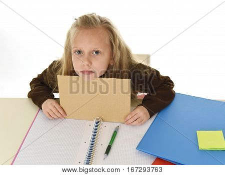 young beautiful little schoolgirl sad tired and bored holding paper with blank copy space for adding text sitting at school desk in stress isolated on white background in education work concept