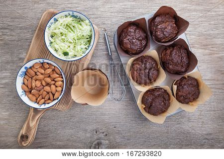 Flourless chocolate courgette muffins in a muffin tin on a wooden table