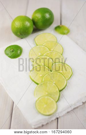 Cut slices of lime on white paper.