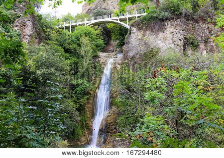 Mountain waterfall with white bridge on the top in National Botanical Garden of Georgia in Tbilisi