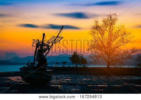 Silhouettes fishing boat and tree at sunset time Phuket Thailand.