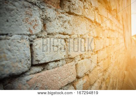 Old red brick wall in a background with sunlight. Selective focus
