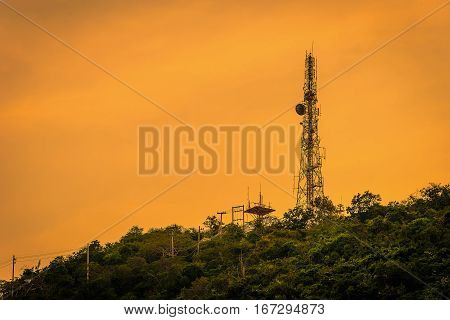 Silhouette telecommunications antenna for mobile phone at sunset