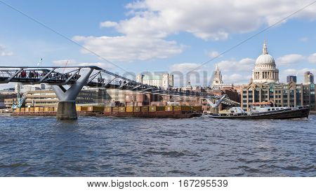 LONDON, UK - MARCH 25, 2016:  Cargo boat passes under Millenium Bridge, with St Pauls Cathedral in background