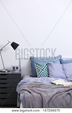 Bedroom interior with bed and nightstand on light wall background