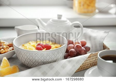 Tasty cornflakes with raspberries and cup of coffee on table