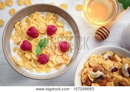 Tasty cornflakes with raspberries and honey on table