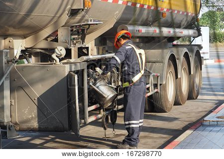 Employees and truck driver oil delivery service to the branch station He put the oil into the cylinder aluminum.