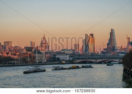 London skyline from Waterloo Bridge over the Thames in London. Taken on a bright December day in the late afternoon as the sun was setting.