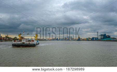 Woolwich ferry crossing the Thames on a stormy day at sunset.  The shot shows the Thames Barrier and the skyline of London beyond.