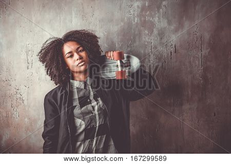 African teenager girl ia a black jacket with blue skateboard in front of a concrete wall