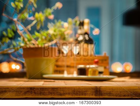 Rustic farmhouse table setting with wine glasses wine bottles and a plant out of focus on a soft blue background.