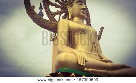 Close up low angle view of golden statue of sitting big Buddha with Samsara Wheel in Thailand