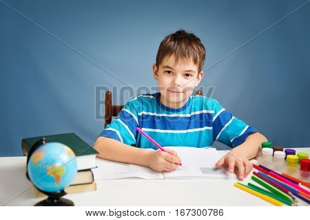 seven years old child writing at home. Boy studying at table on blue background. Kid drawing with a pencil