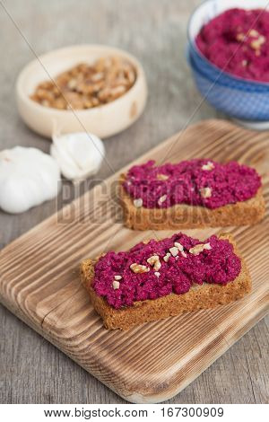 Beetroot pesto in a blue bowl on a wooden table with garlic beetroot and almond bread selective focus