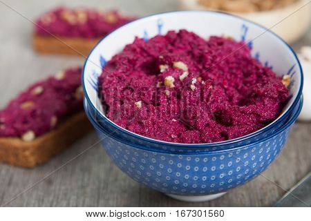Beetroot pesto in a blue bowl on a wooden table with garlic beetroot and almond bread on the back selective focus