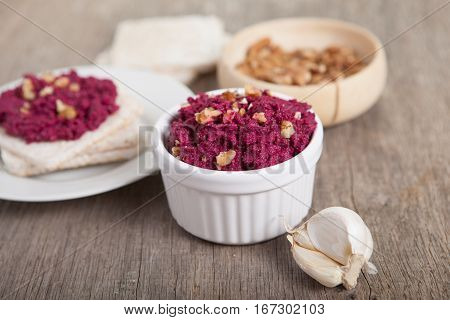 Beetroot pesto in a white bowl on a wooden table with garlic beetroot and rice cakes on the back, selective focus