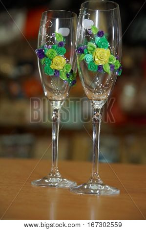 beautiful holiday decor for wedding: glasses of thin glass decorated with garlands of flowers from polymer clay