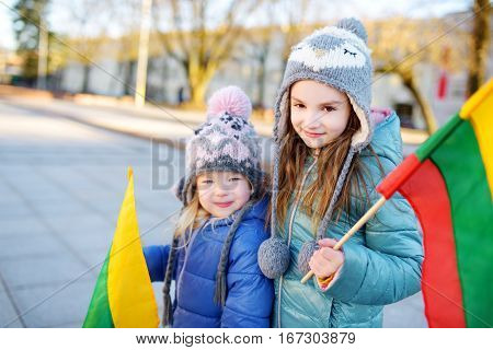 Two Adorable Little Sisters Celebrating Lithuanian Independence Day Holding Tricolor Lithuanian Flag