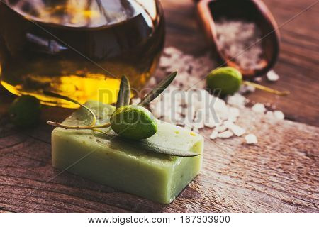 Natural spa setting with olive and olive oil products: bath salt natural soap and olive oil.
