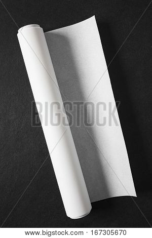 Roll of white baking paper photographed overhead on slate with natural light