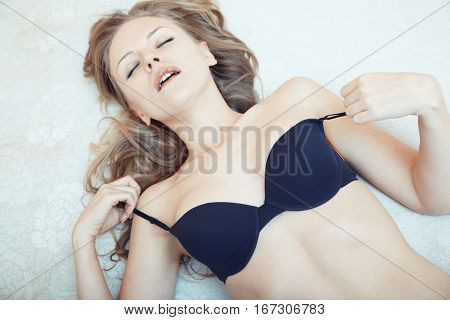 Blond lady laying on the bed and taking pleasure