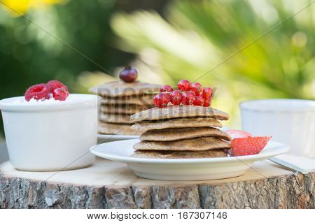 Breakfast in the garden: paleo style grain free banana almond pancakes coconut yogurt with berries selective focus on redcurrants