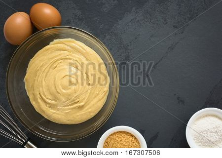 Basic homemade cake or cookie dough in glass bowl with ingredients and whisk on the side photographed overhead on slate with natural light