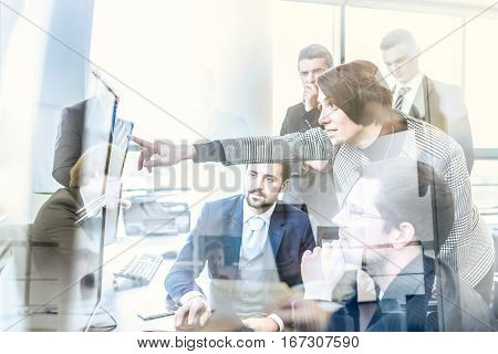 Business team looking at data on multiple computer screens in corporate office. Businesswoman pointing on screen. Business people trading online. Business, entrepreneurship and team work concept.