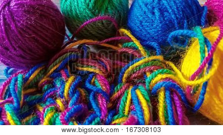 Multicolored yarn balls and knitted garment background