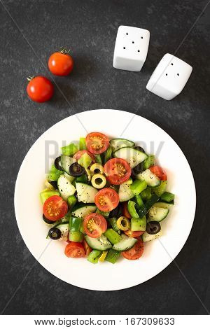 Fresh salad of black and green olives cherry tomatoes green bell pepper and cucumber seasoned with salt pepper dried oregano and basil photographed overhead on slate with natural light