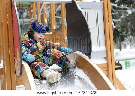 Boy Sitting On Slide
