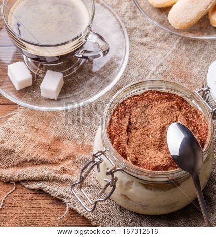 Photo of wooden table with tiramisu, biscuits Savoiardi, coffee cup