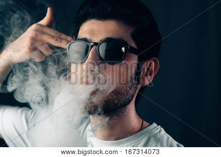 Young cool guy in sunglasses exhales a cloud of smoke With finger to his temple. Studio horizontal portrait in close-up