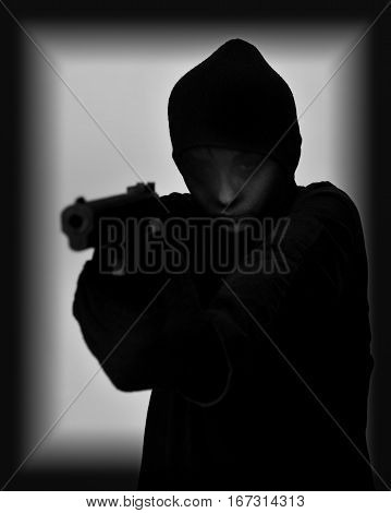 Female robber with black tights over her head holding a gun and aiming. Black and white. Low key. Selective focus.