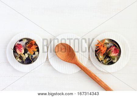 Containers with dried aromatic medicinal flowers on cotton pads, wooden spoon, empty space white wooden table background, top view set.