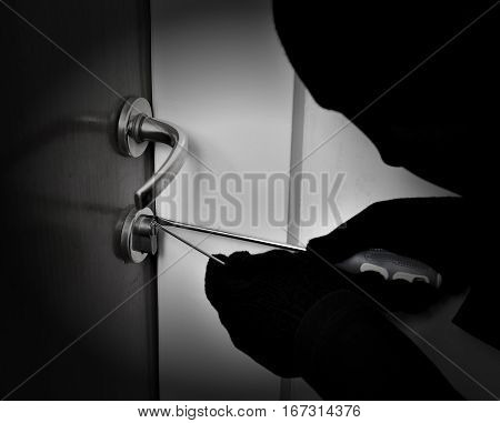 Robber with black tights over the head breaking the door lock. Black and white. Low key. Selective focus.